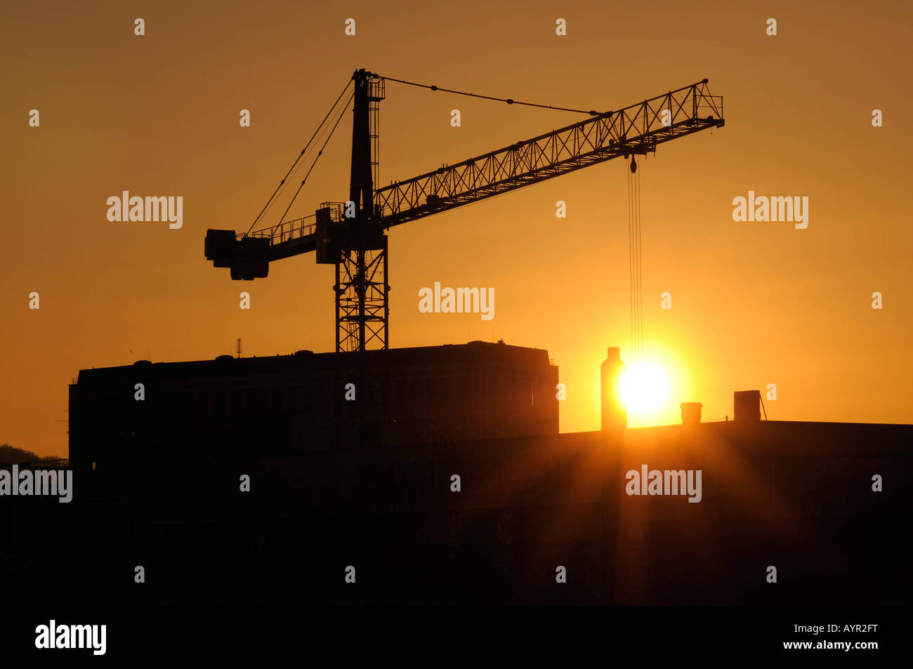 Construction crane at a building site, setting sun - Stock Image