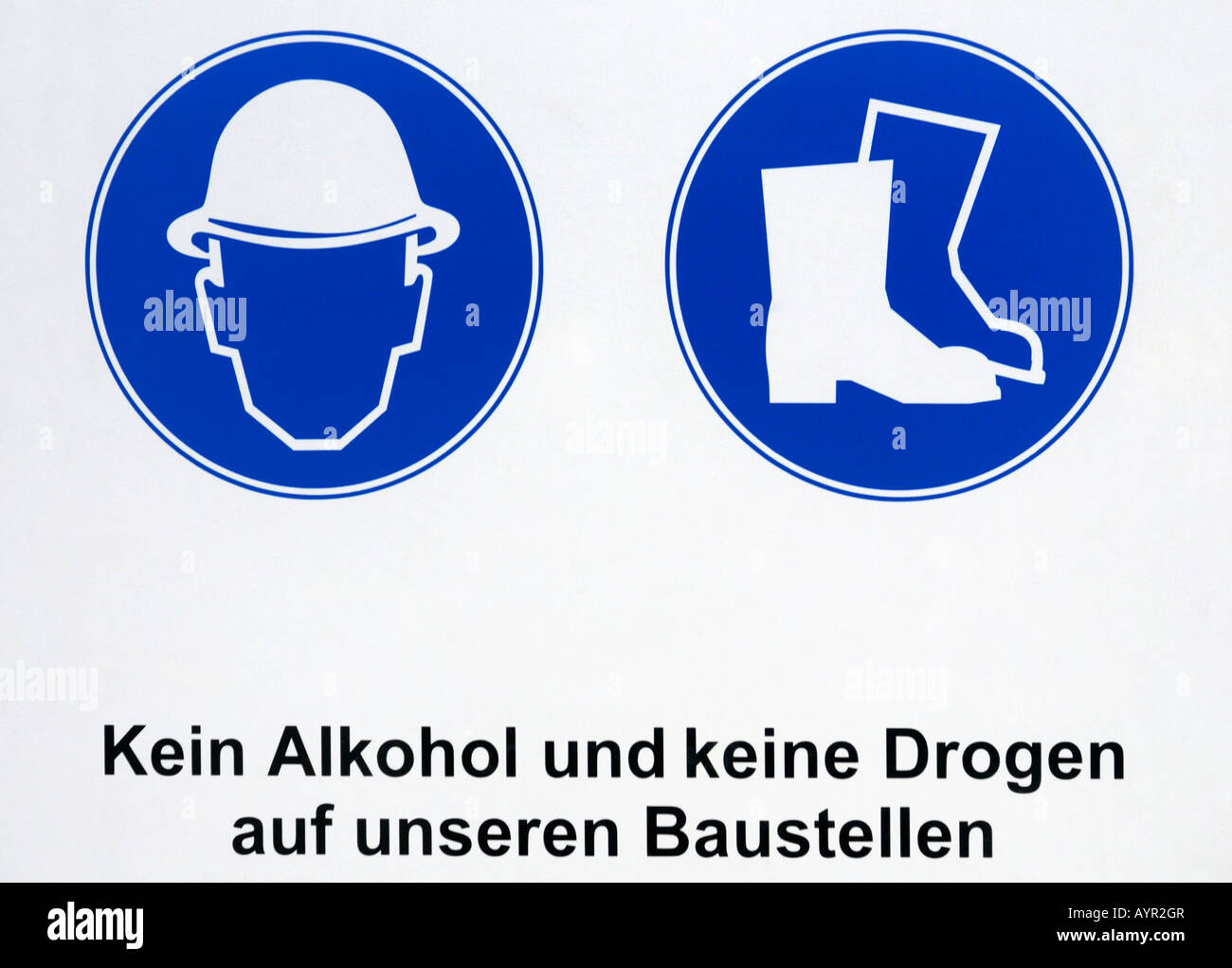 "Sign at a construction site: pictures showing hardhat and steel-toed boots must be worn and the words (German) ""No drugs or alc Stock Photo"