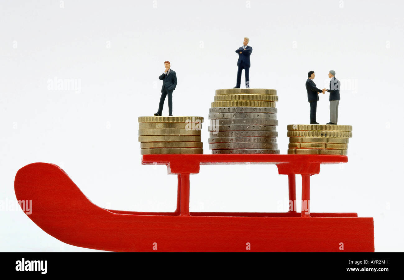 Businessmen standing on stacks of Euro coins on a red sleigh - Stock Image