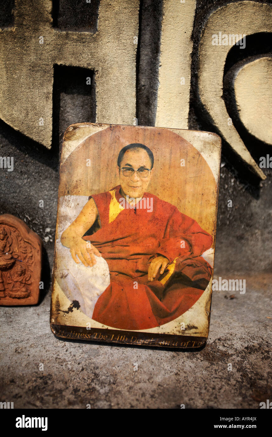 Close up detail image of a faded photograph of the Dalai Lama on a Buddhist shrine. - Stock Image