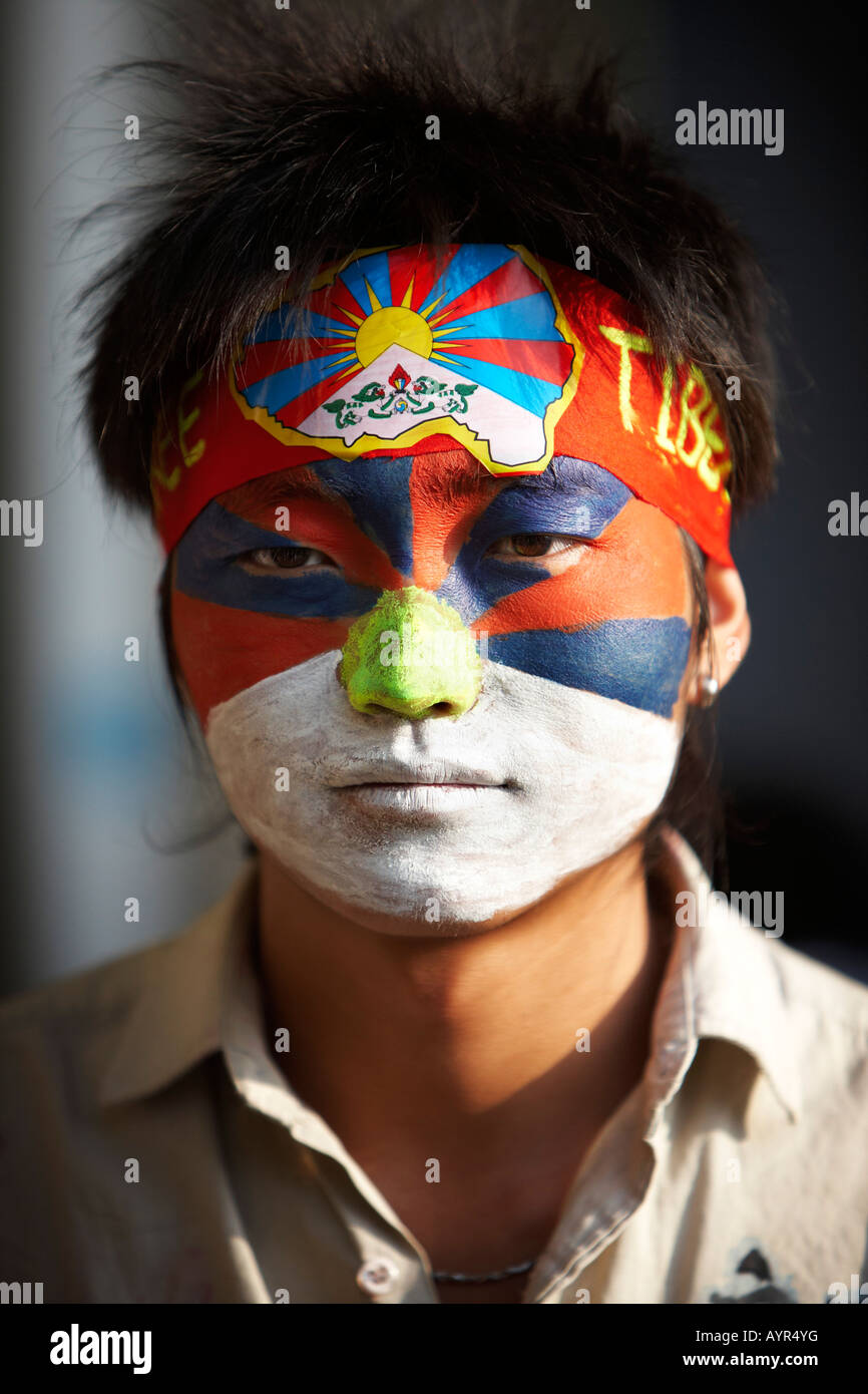 Portrait of an exiled Tibetan protestor with the Tibetan flag painted on his face. - Stock Image