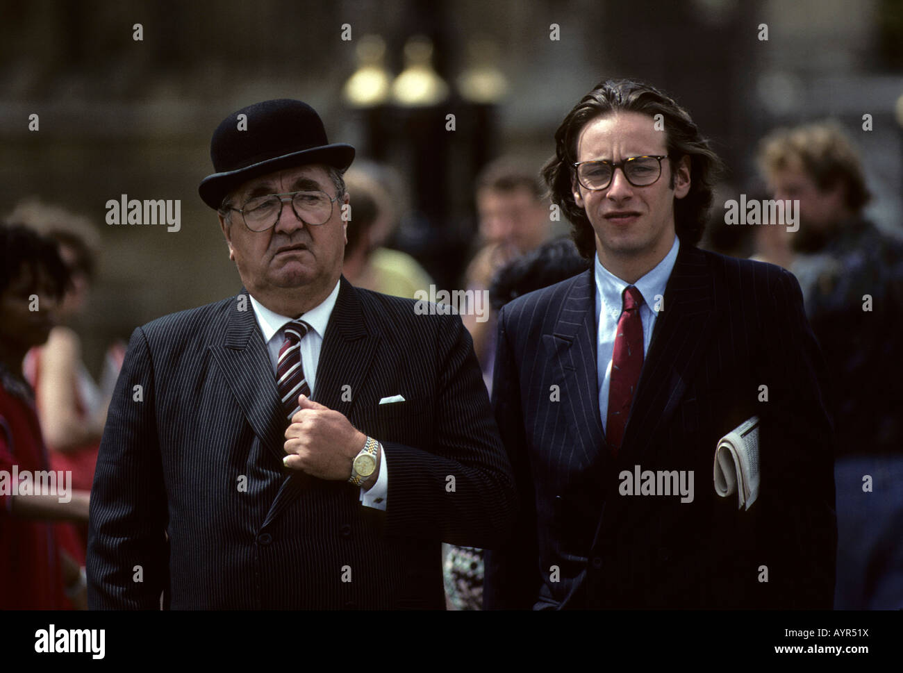 cc120820017 Older man wearing bowler hat and young man wearing pin-striped suit with  newspaper under