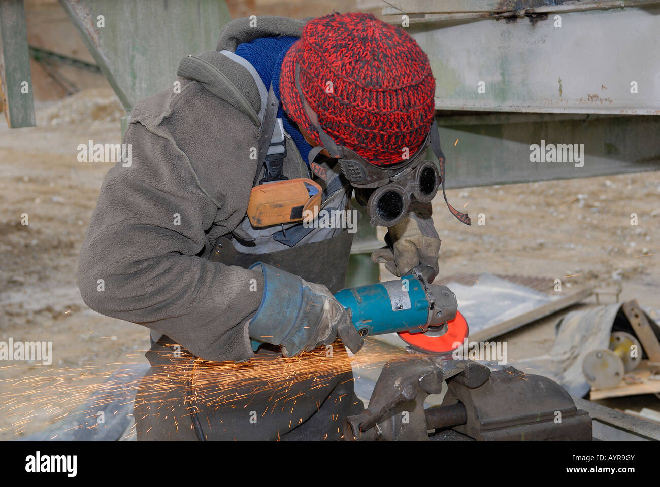 Man working metal with angle grinder - Stock Image