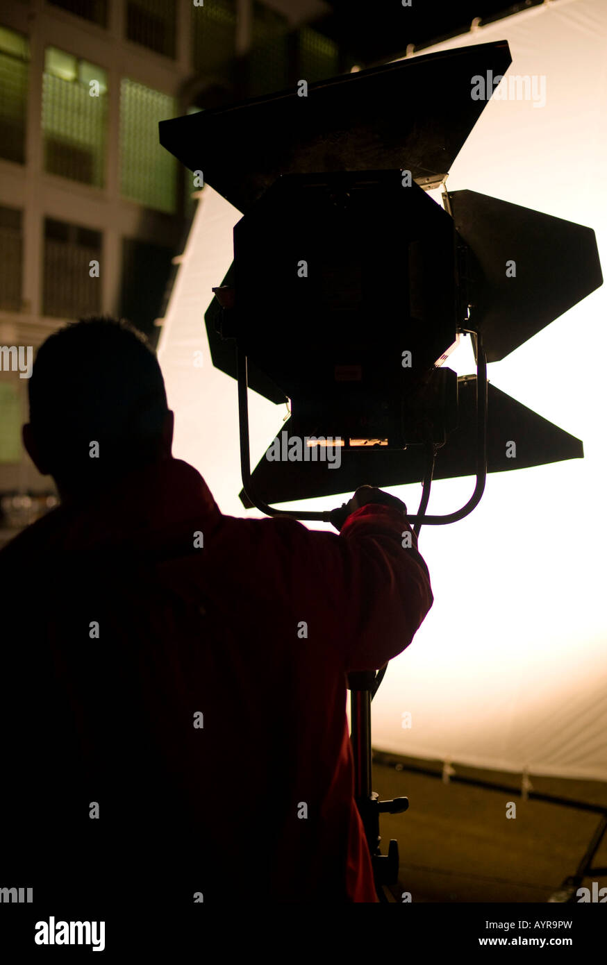 Lighting technician setting up a floodlight on a film set in Germany, Europe - Stock Image