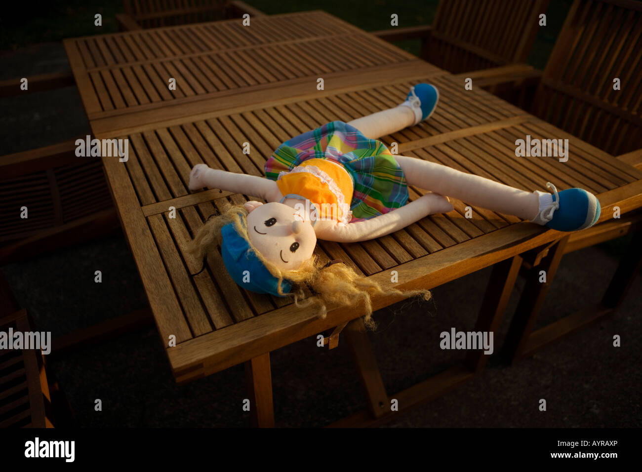 Soft toy doll on a table, outside in a garden, in evening sunlight - Stock Image