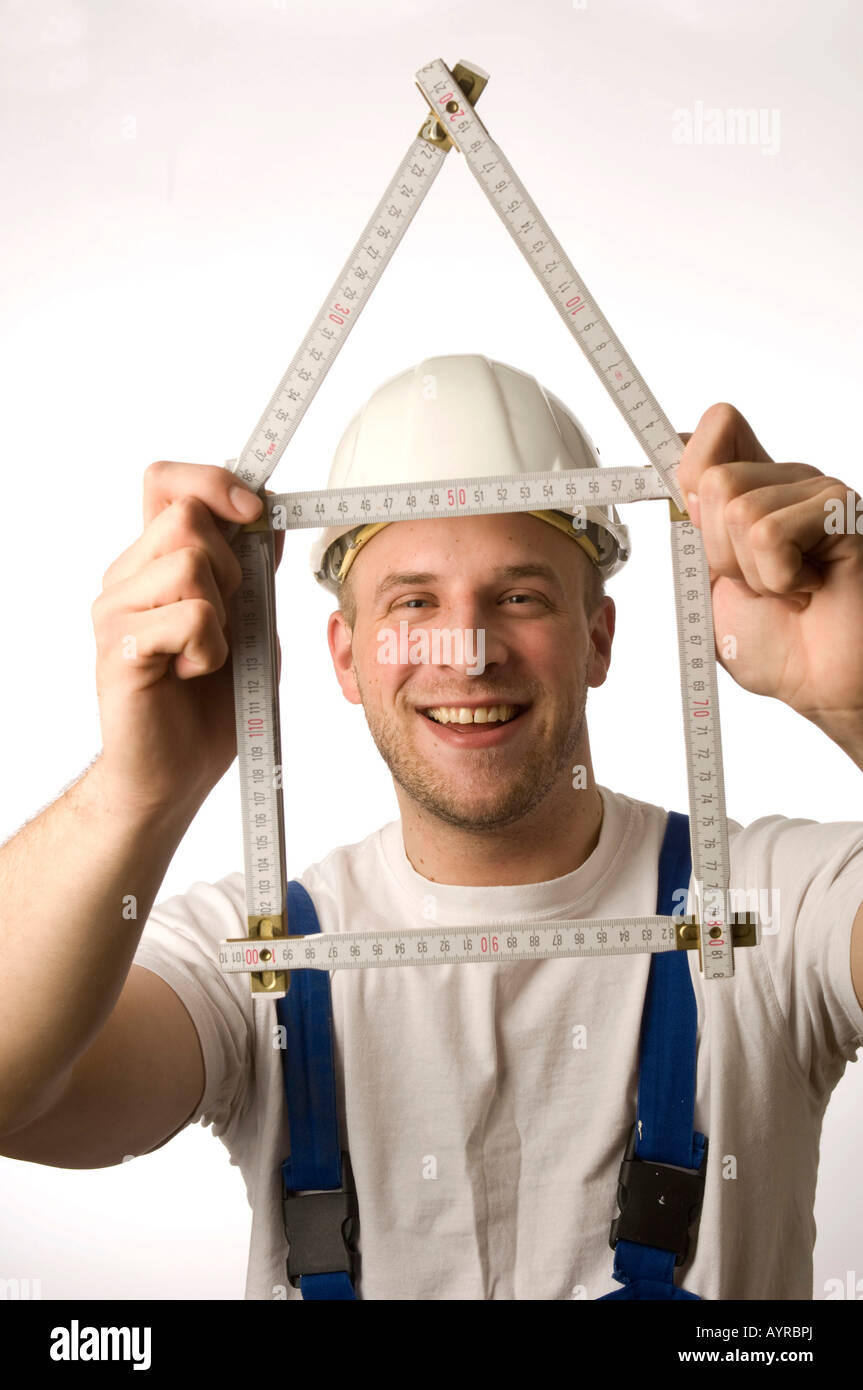 Construction worker holding folding rule (yardstick) - Stock Image