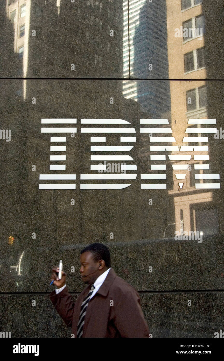 MAN SPEAKING ON MOBILE PHONE WITH IBM LOGO ON IBM BUILDING MIDTOWN MANHATTAN NEW YORK CITY UNITED STATES OF AMERICA USA - Stock Image