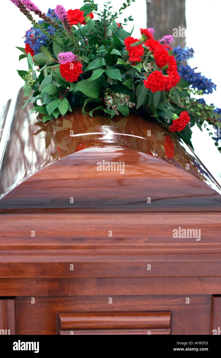 Coffin at cemetery with sand cross and bouquet of flowers. Buffalo Minnesota USA - Stock Image