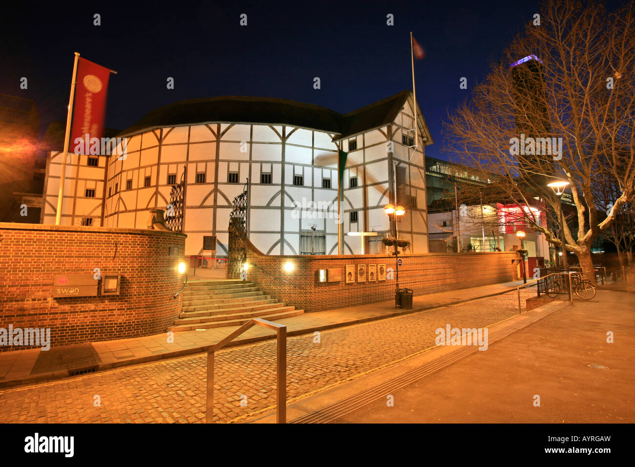 Shakespeare Globe Theatre on the southern bank of the Thames at dusk, London, England, UK - Stock Image