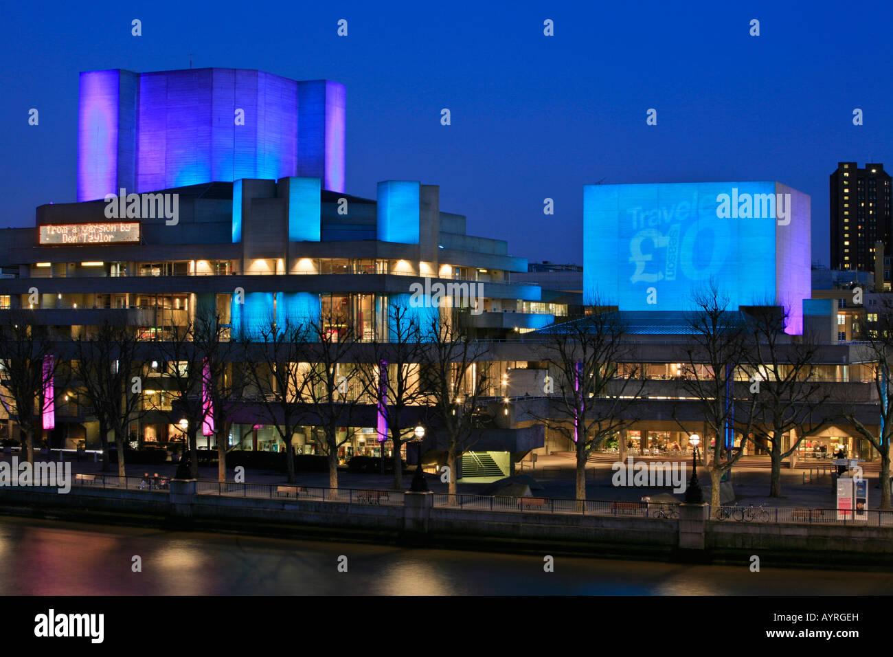 National Theatre building illuminated blue at dusk, London, England, UK - Stock Image