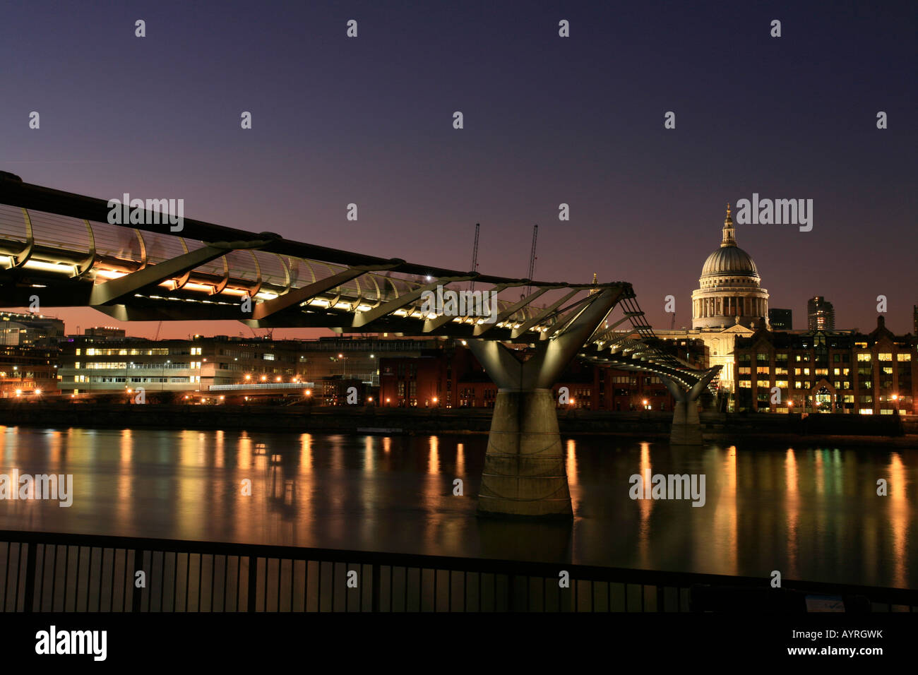 St. Paul's Cathedral and Millennium Bridge at dusk, seen from southern bank of the Thames, London, England, - Stock Image
