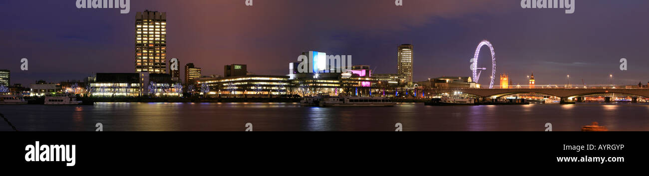Panoramic view of South Bank, the illuminated National Theatre, London Eye ferris wheel and Westminster Palace (back), - Stock Image