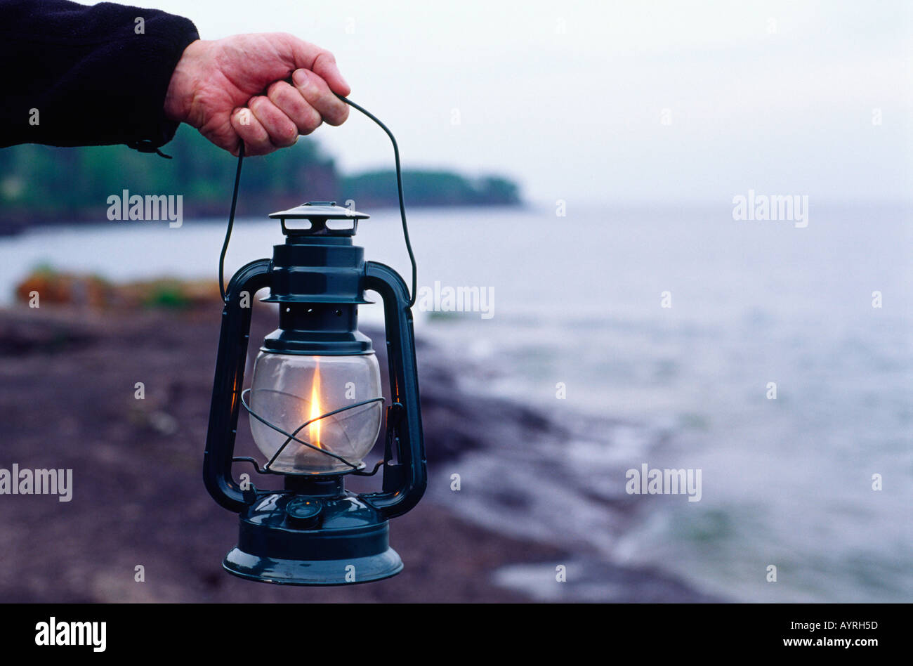 Man hand holding liquid gas fuel lantern on the rocky shore of Lake Superior Minnesota MN USA - Stock Image
