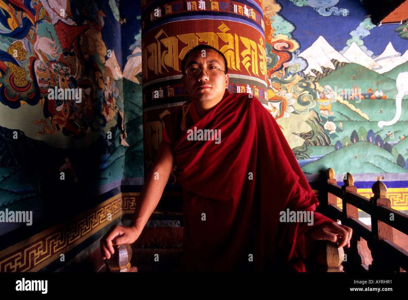 Buddhist monk with the prayer wheel behind, Bhutan Stock Photo