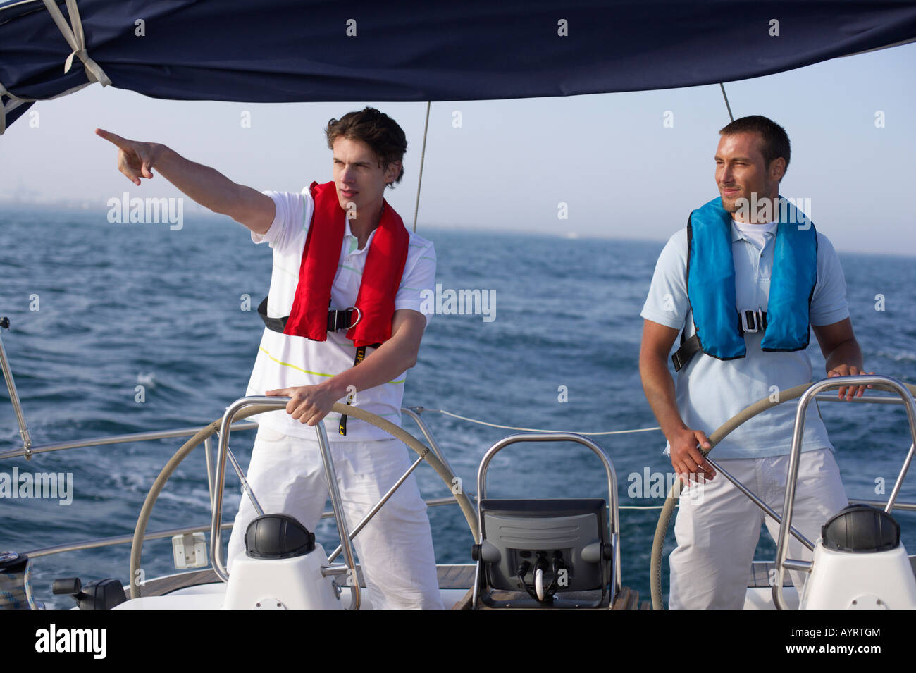 Two men steering a boat Stock Photo