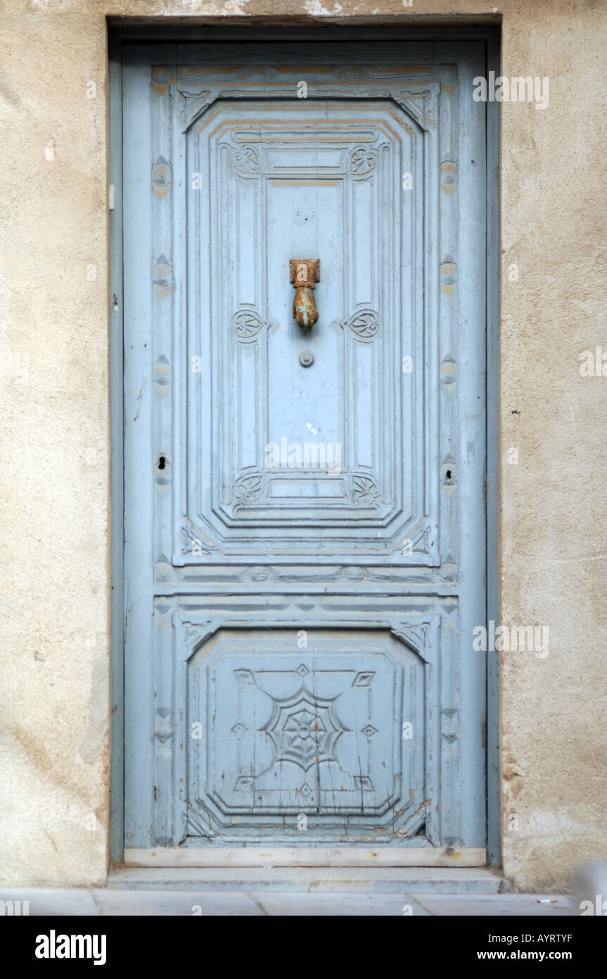 hand and wrist door knocker on blue powder background castello d'empuries catalonia / catalunya costa brava spain - Stock Image