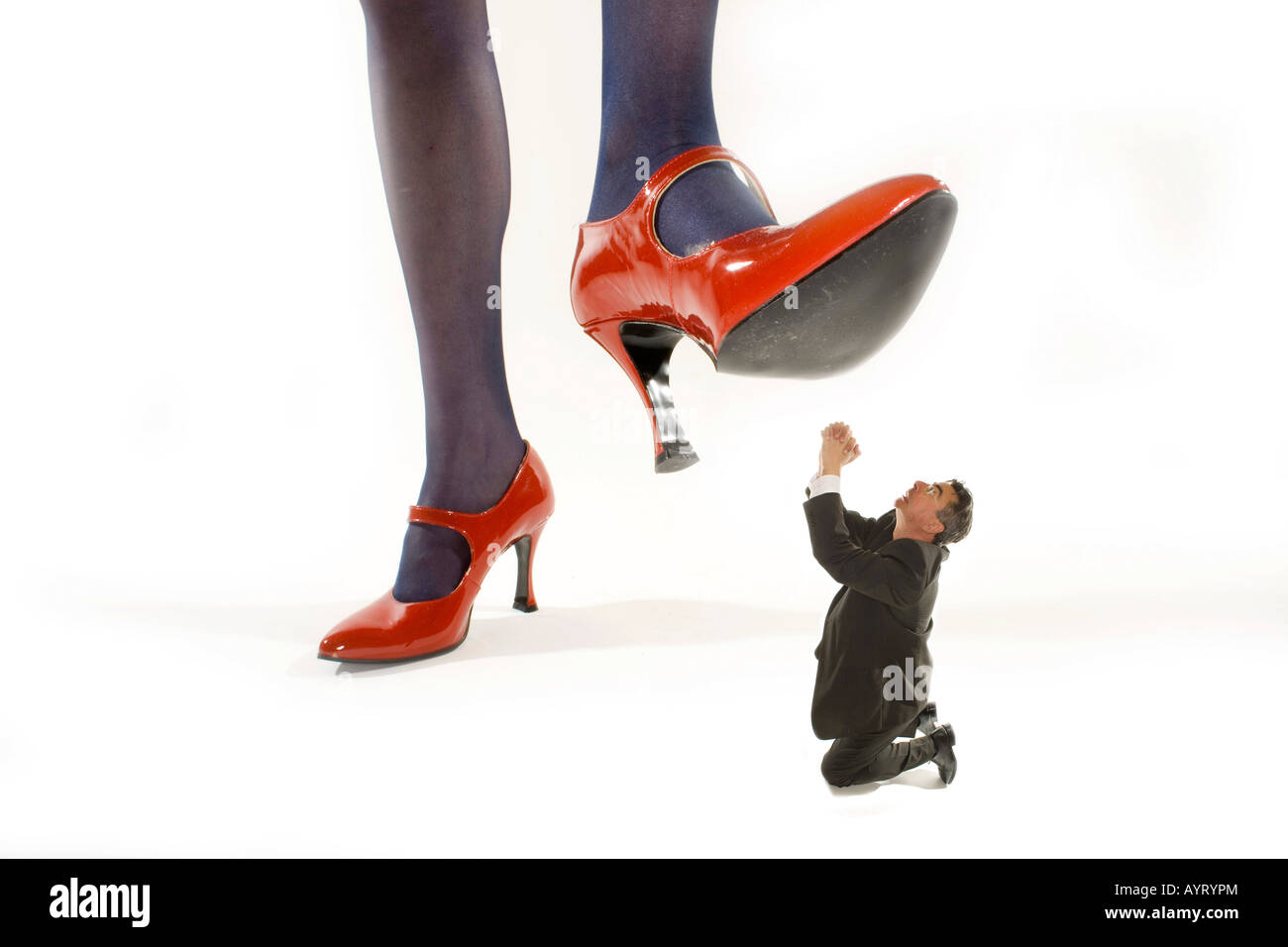 Woman in red high heels stepping on a shrunken man - Stock Image