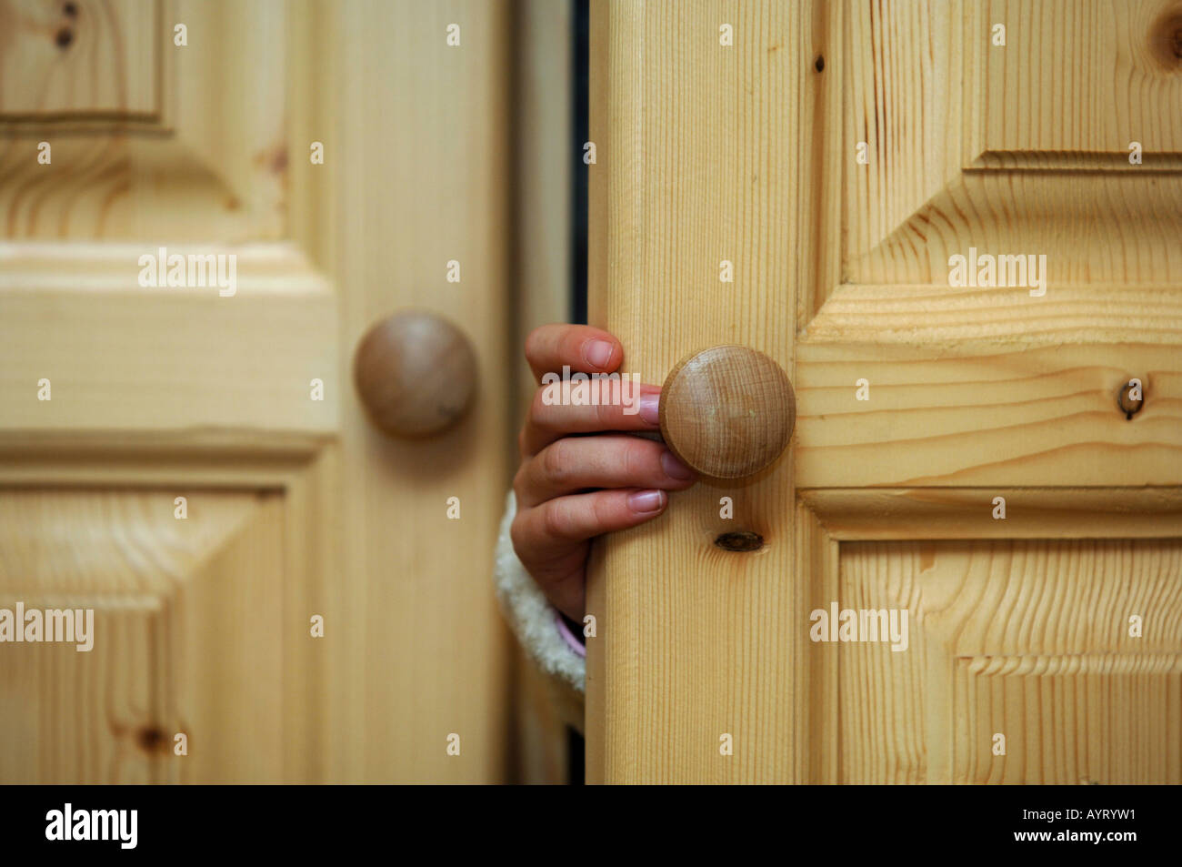 Hand of a child opening a cupboard doorStock Photo