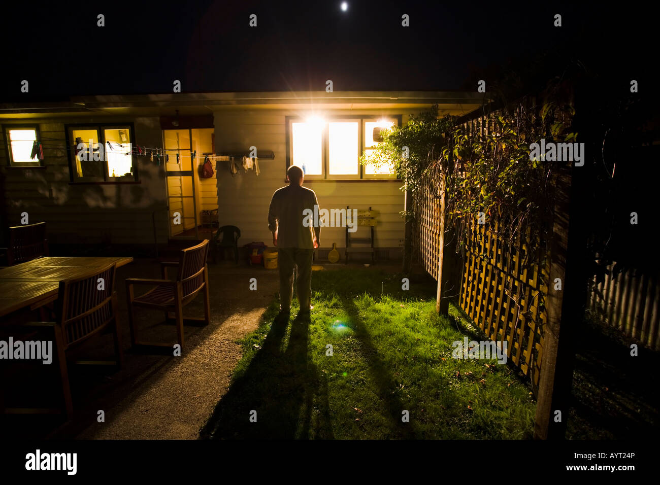 Watching through the window, man looks in house from garden at night in darkness Stock Photo
