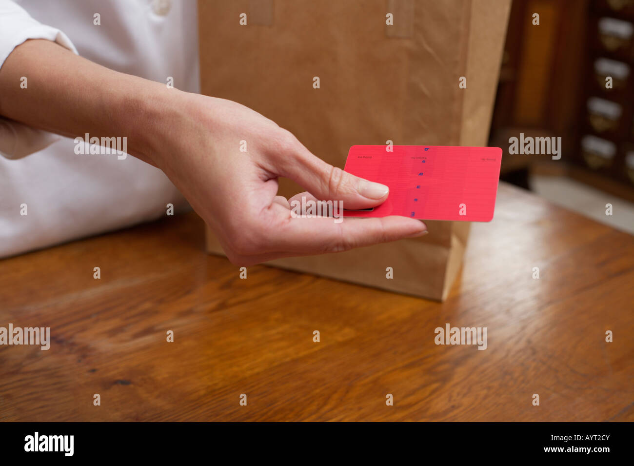 Female pharmacist holding a red card - Stock Image