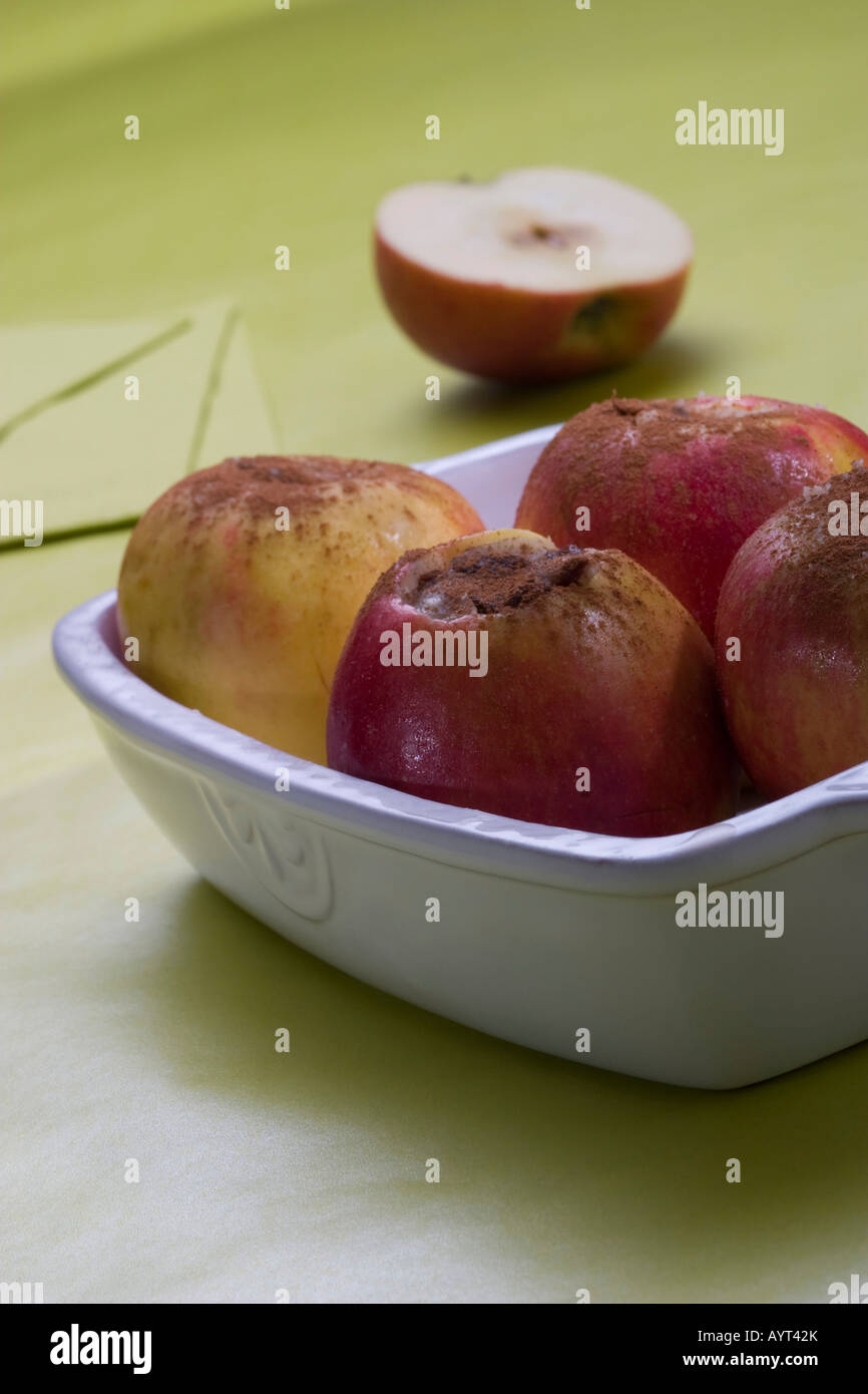 Several apples filled with marzipan and dusted with cinnamon in a bowl - Stock Image