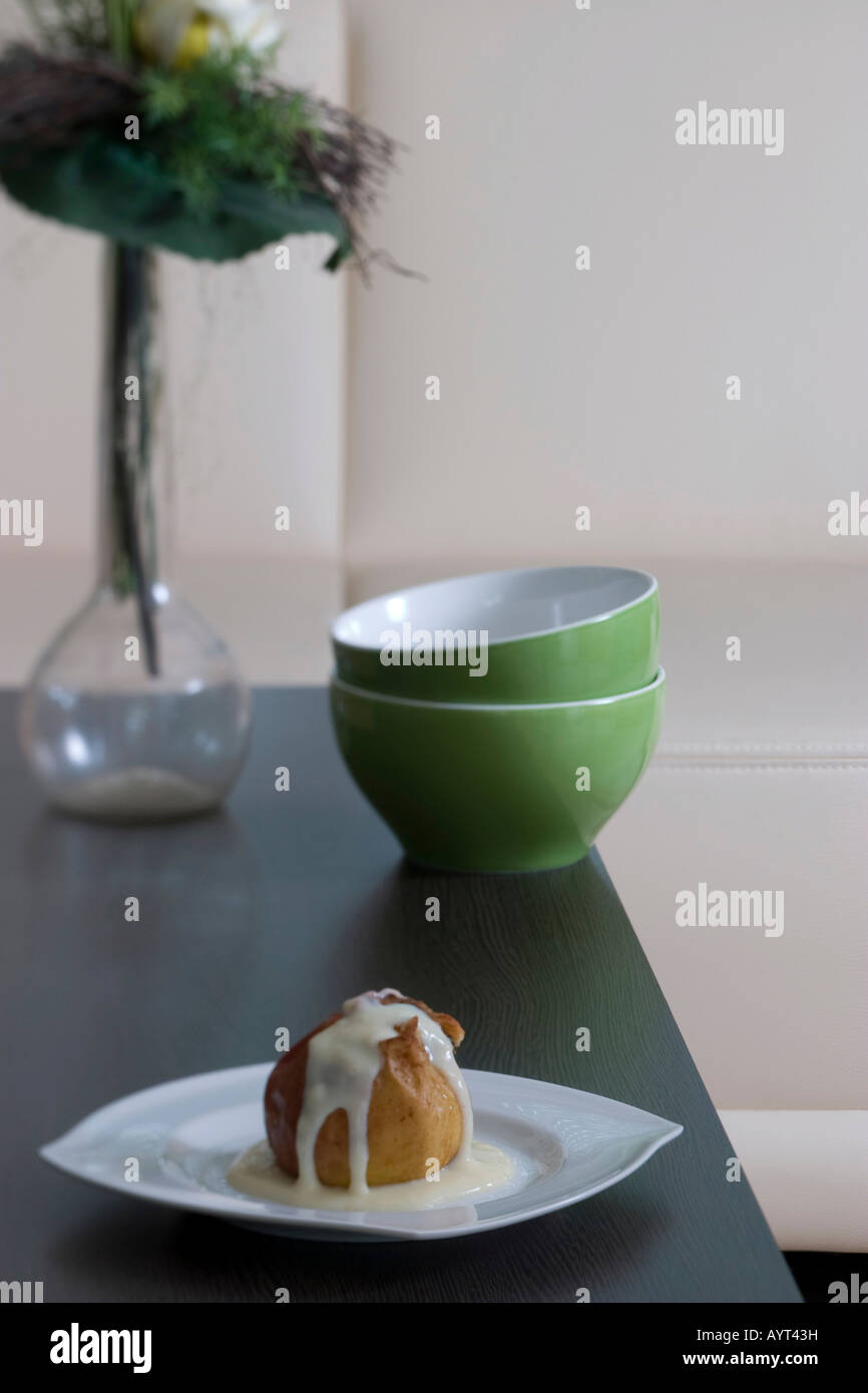 Baked apple filled with marzipan, dusted with cinnamon and covered in vanilla sauce on a plate, served in living - Stock Image