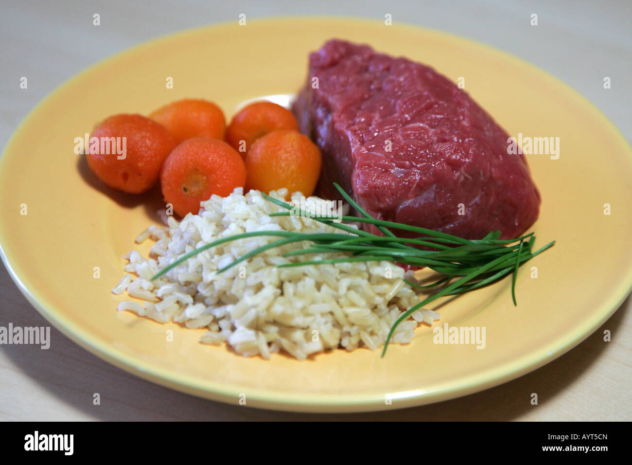 Raw meat with uncooked vegetables and rice, ready for preparation Stock Photo