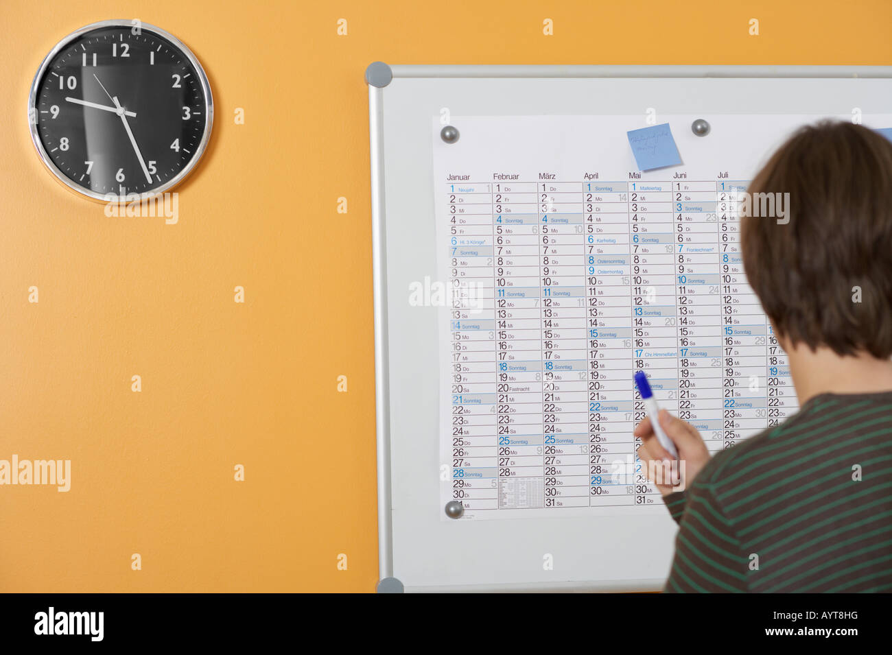 A man is standing in front of a annual calendar - Stock Image