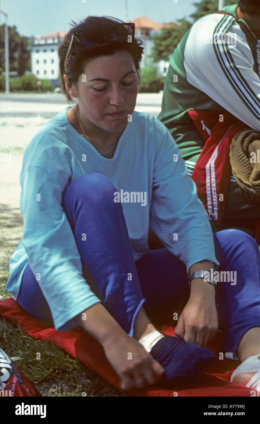Young Pilgrim Tending to Aching Feet on route to Fatima Portugal - Stock Image
