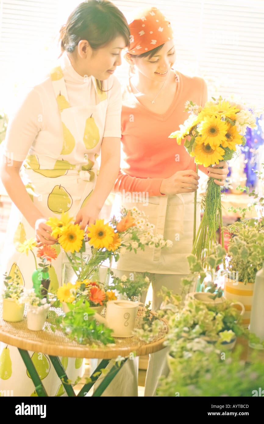 Two women arranging flowers in the transparent vase - Stock Image