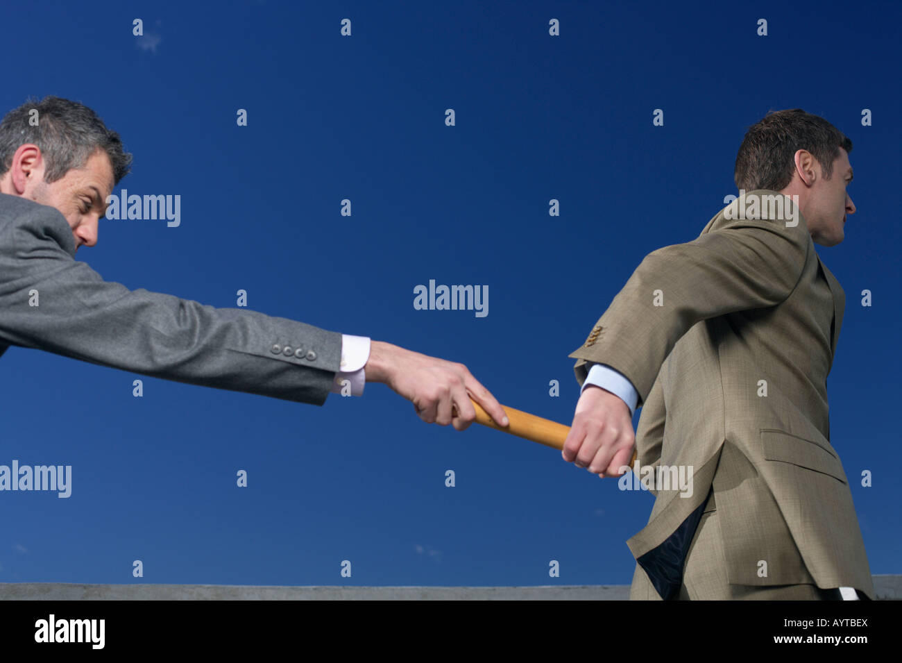 Businessman passing baton to colleague - Stock Image