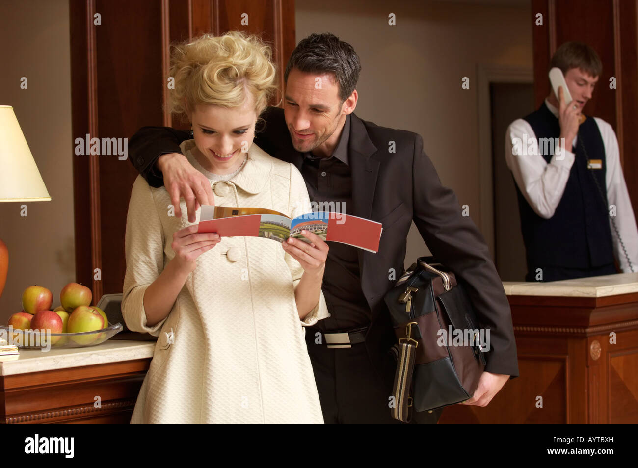 Couple reading a hotel flyer - Stock Image