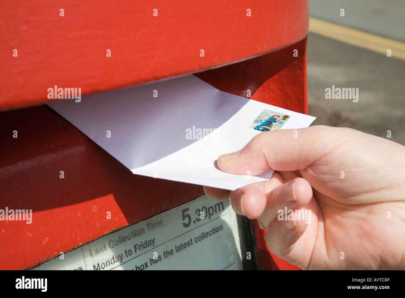 Close-up of person's hand holding posting a letter with 2nd class stamp to post in a red postbox. England UK Stock Photo