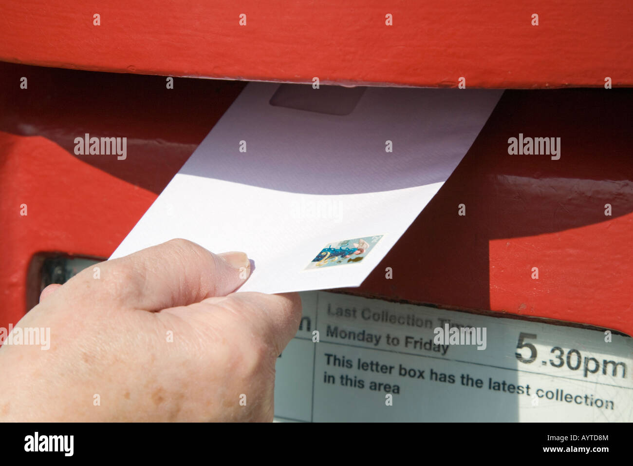 England UK Close-up of person's hand holding letter with 2nd class stamp to post in red postbox - Stock Image