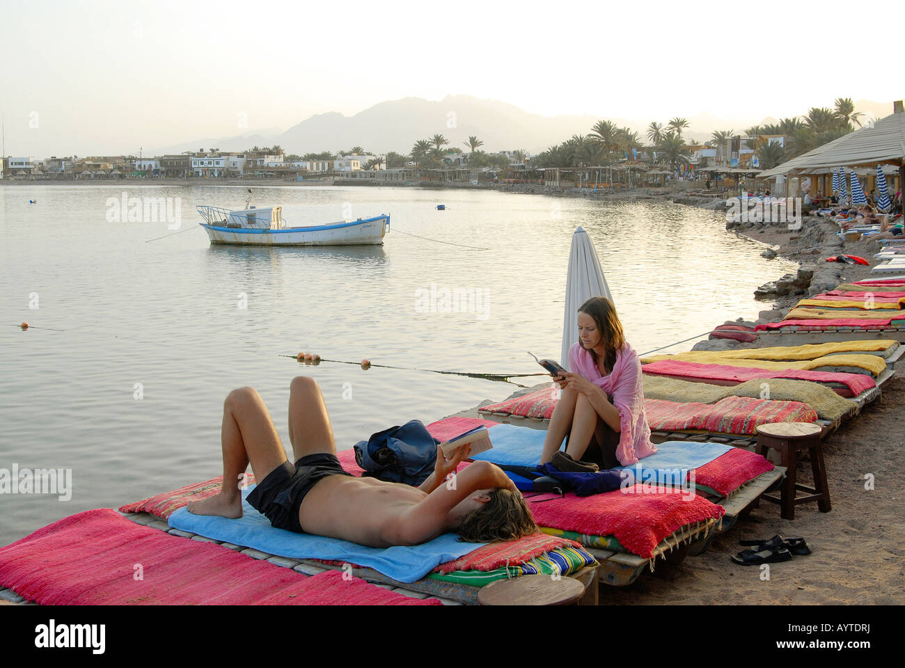 Tourists are enjoying the sunset at the beach in Dahab, Egypt - Stock Image