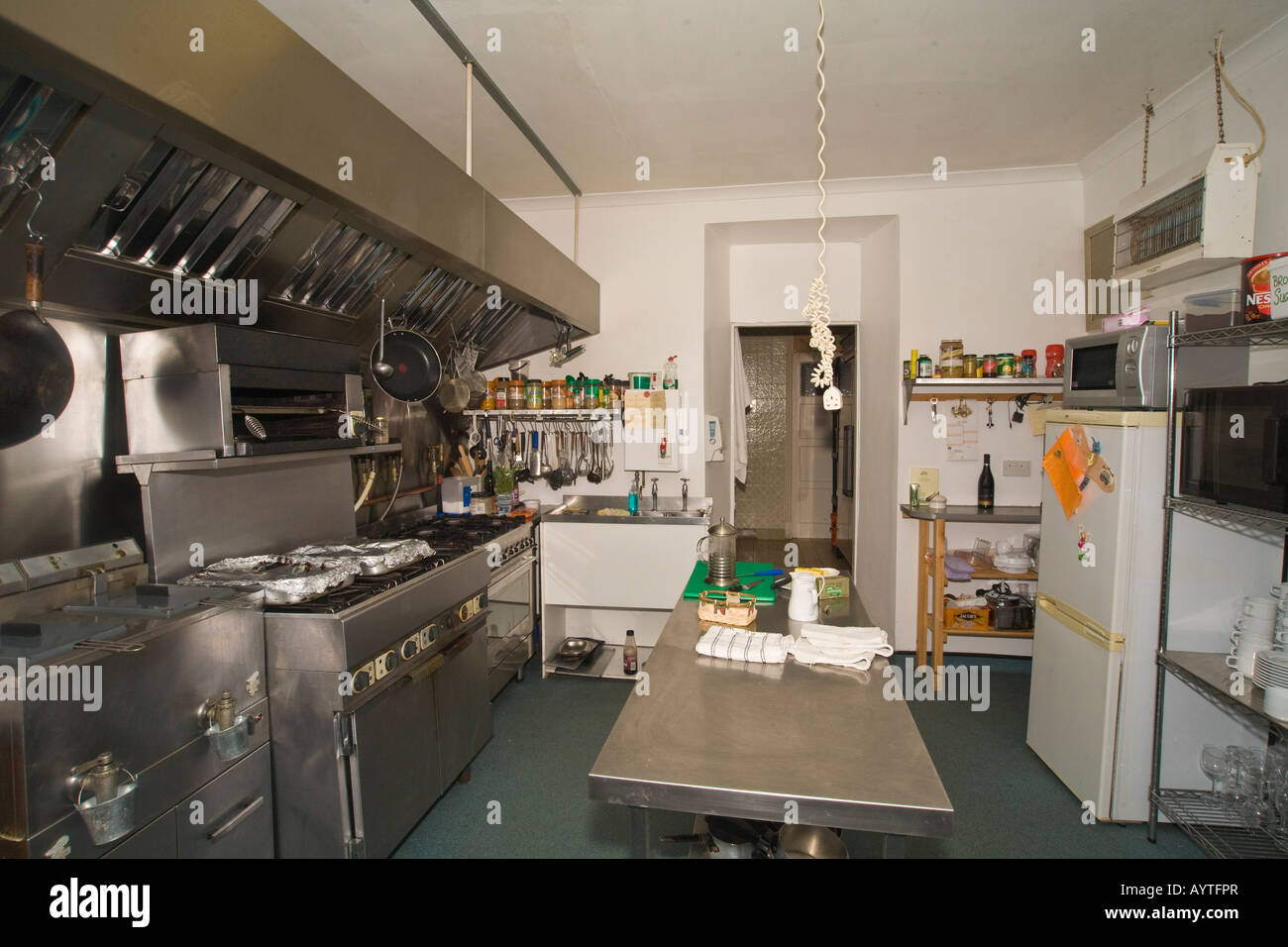 Hotel kitchen with cookers fridge and showing food preparation area - Stock Image