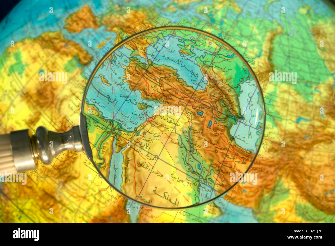 Part of world Middle East Region globe written in Arabic seen through magnifying glass - Stock Image