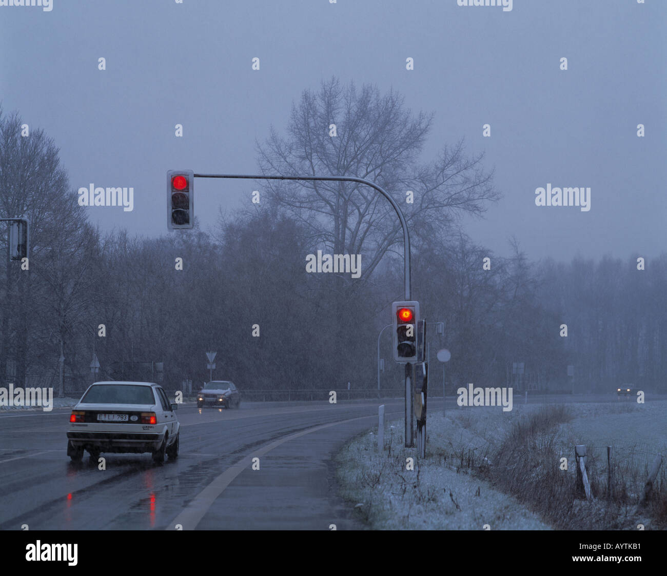 bad weather, rain, slush, sleet, country road, cars driving with lamplight during the day, traffic light showing Stock Photo