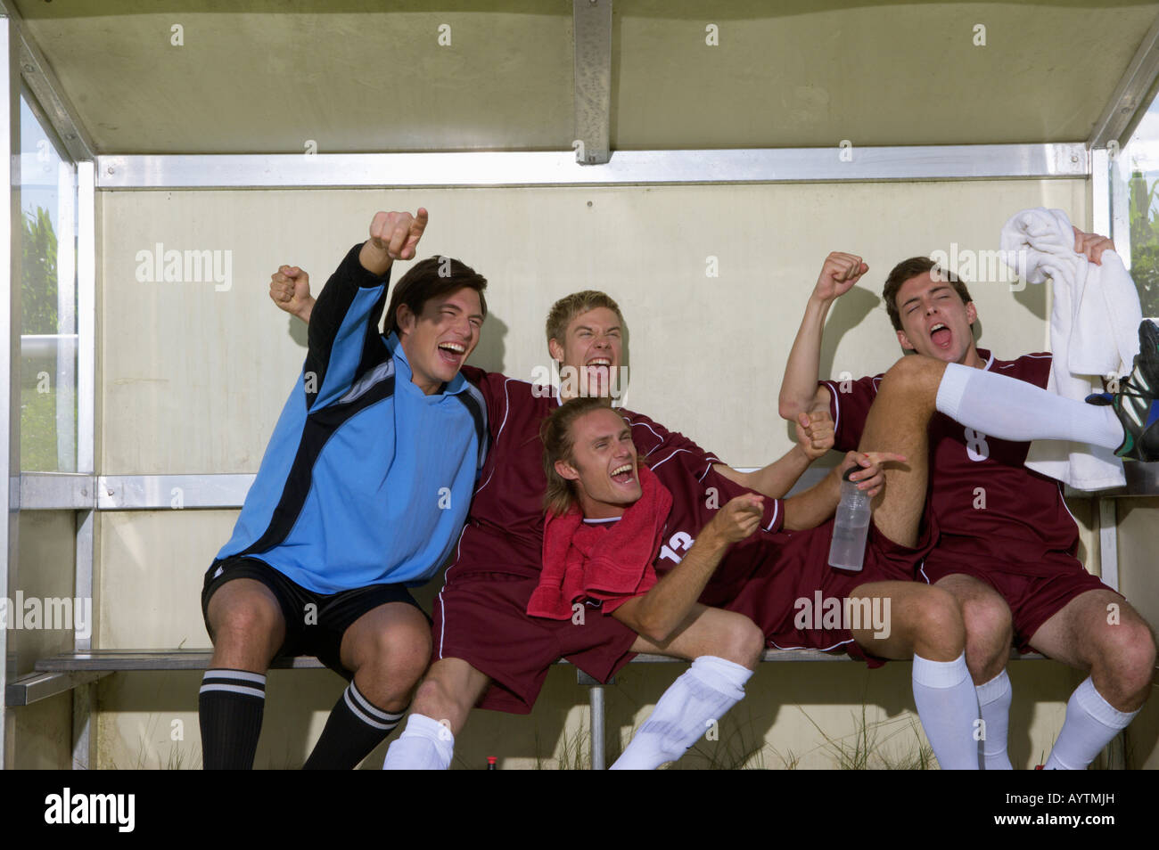 Cheering kickers sitting on substitutes' bench - Stock Image