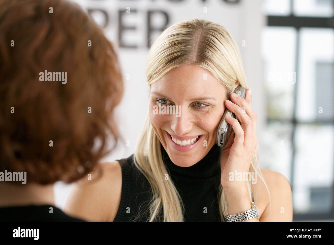 Two young women vis-à-vis, one woman phoning with a mobile phone - Stock Image