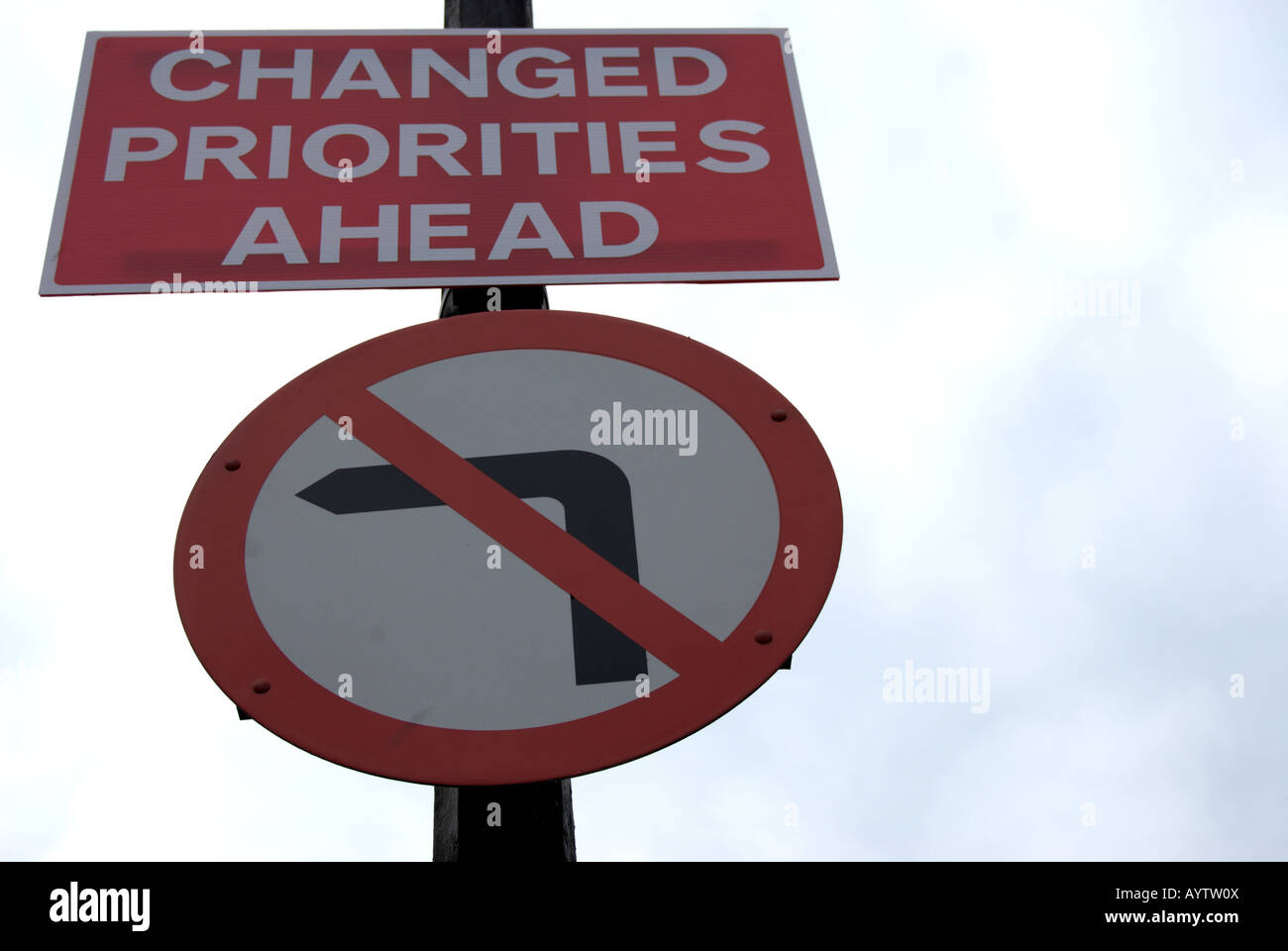 british road sign fixed to to a lamppost indicating no left turn and stating changed priorities ahead - Stock Image