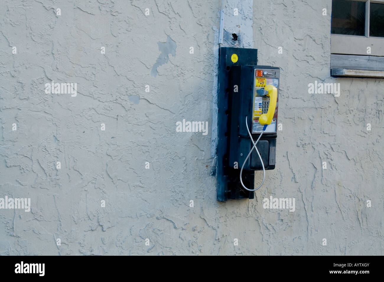 Old yellow payphone on a wall - Stock Image