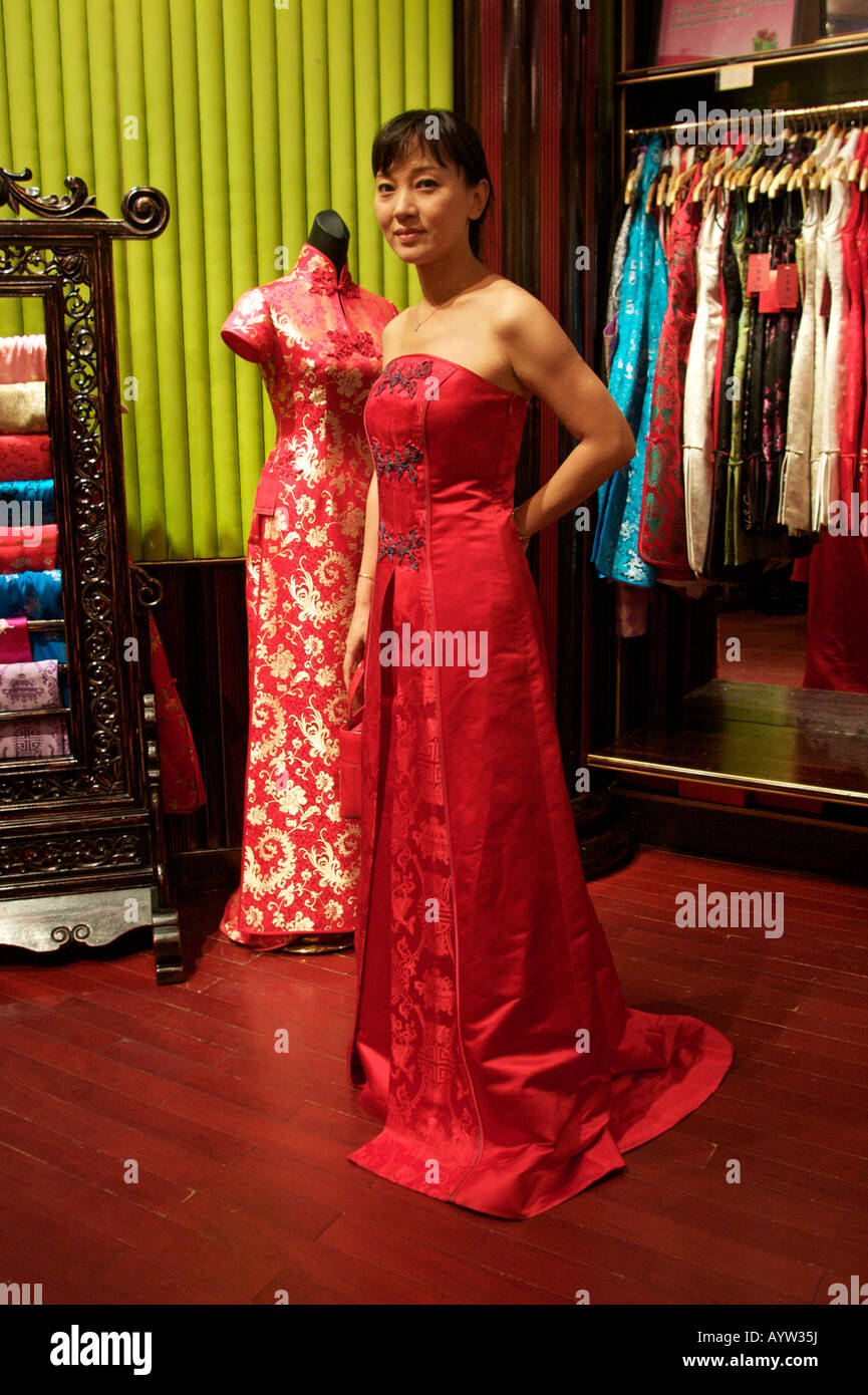 1ebce1b74 A woman tries on a traditional Chinese silk dress for sale at the Oriental  plaza mall Beijing China