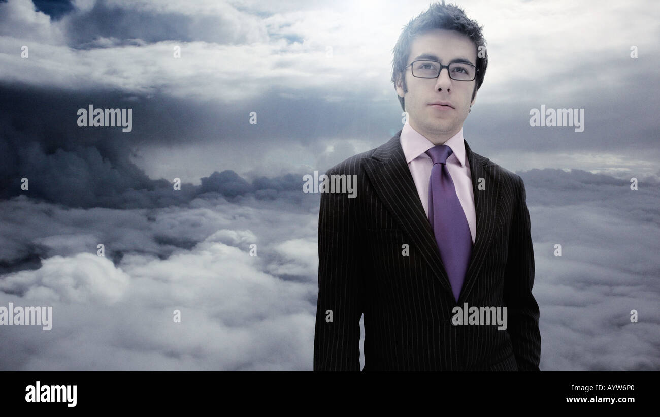 Suited business man with a cloudy sky background - Stock Image