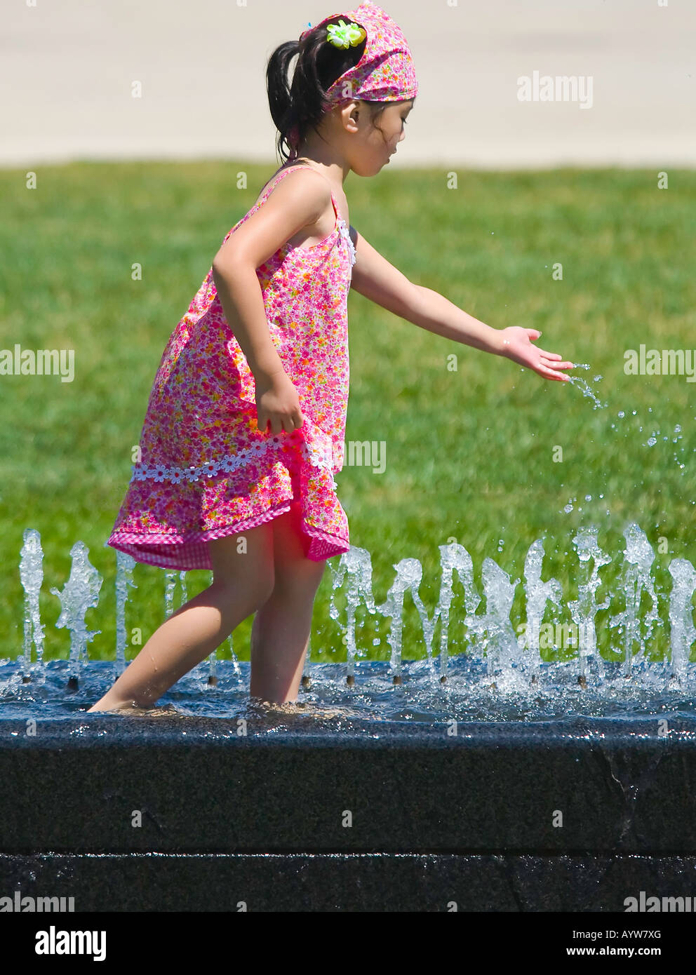 Young Asian girl playing in a fountain - Stock Image