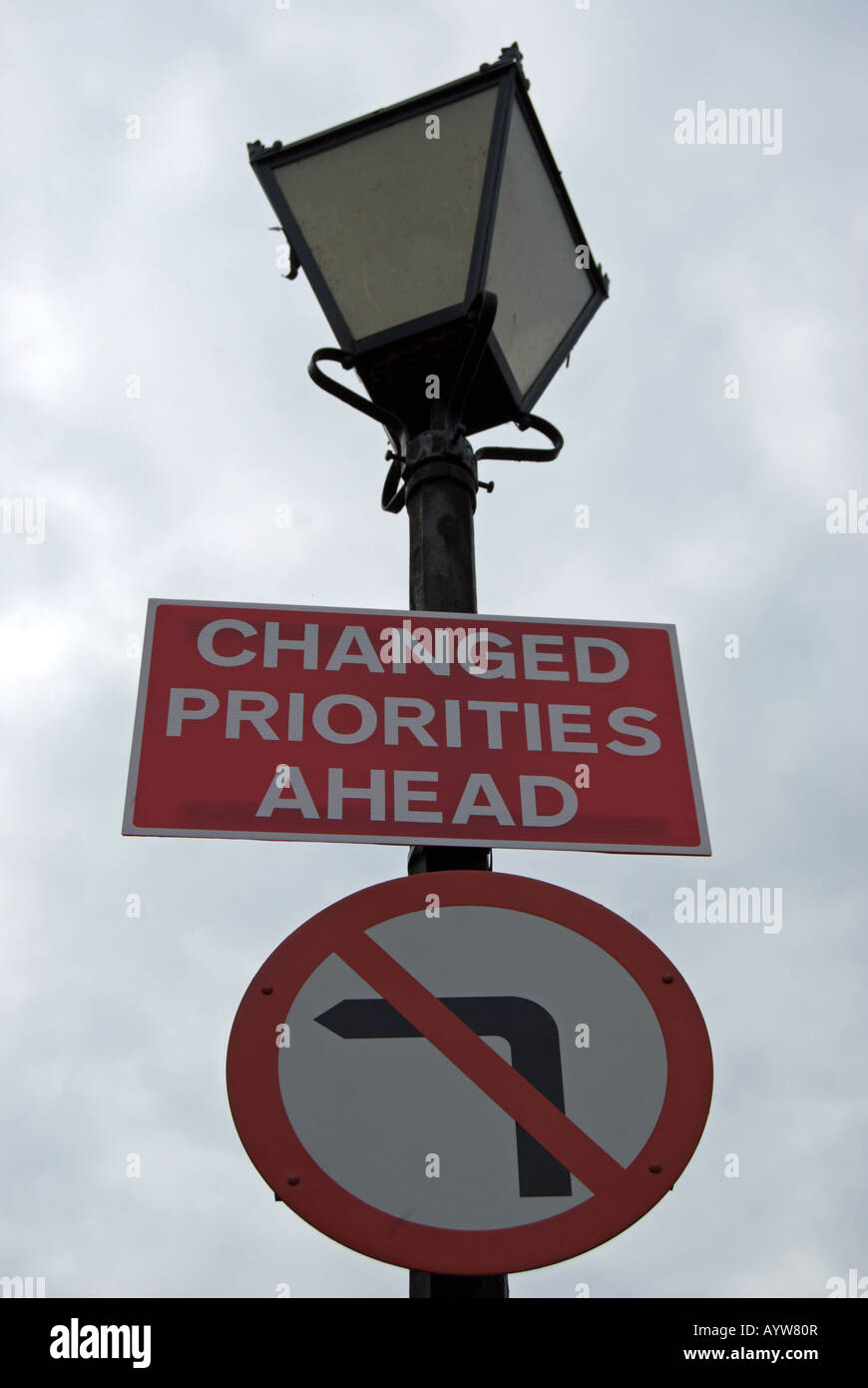 british road sign fixed to victorian style lamppost indicating no left turn and stating changed priorities ahead - Stock Image