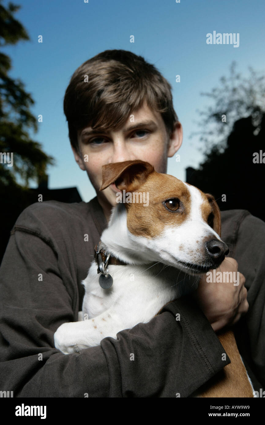 Boy holding an inquisitive jack russell dog - Stock Image