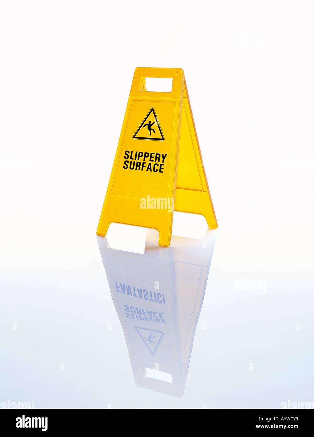 A bright yellow warning floor sign saying 'Slippery surface' on a wet / icy background - Stock Image