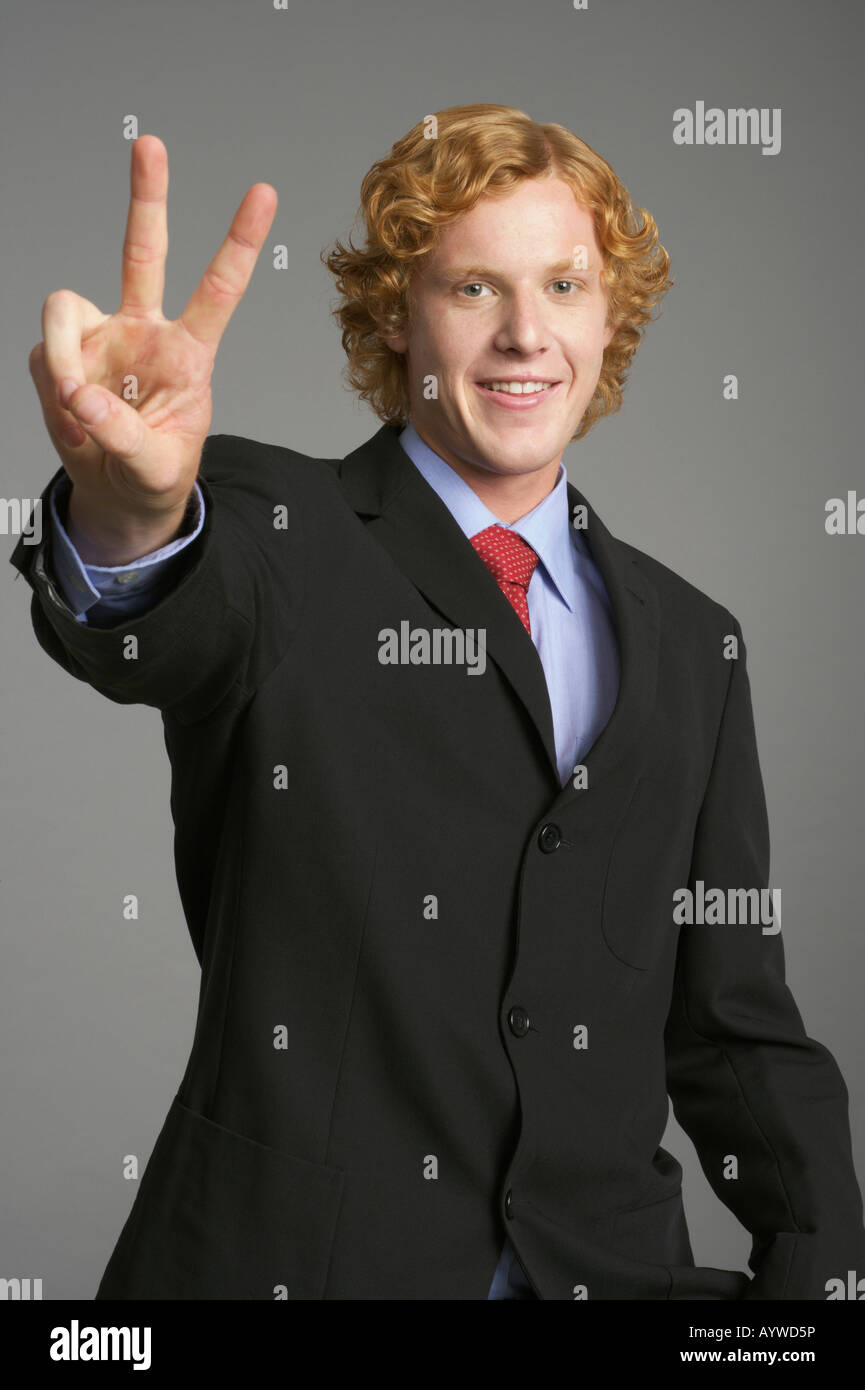 Businessman making peace sign - Stock Image