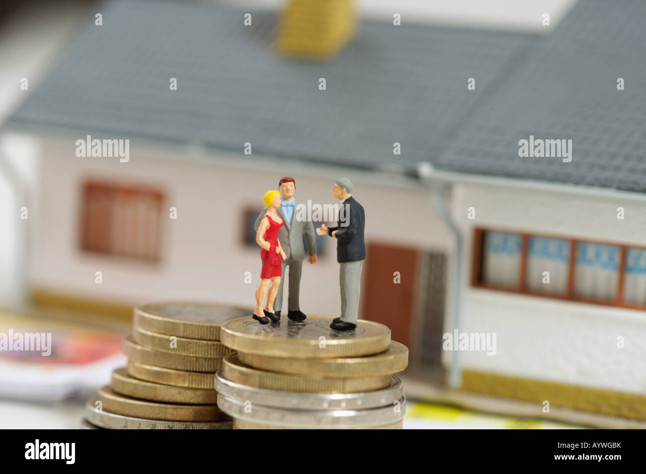Figurines on a stack of coins, miniature house in background - Stock Image